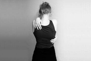 Desperate woman embracing herself in black and white
