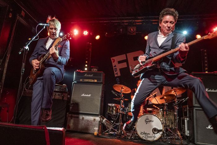 From The Jam band Bruce Foxton jumping on stage with bass guitar