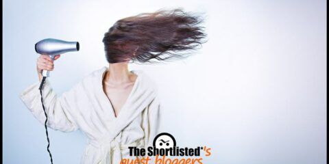 Funny windy air dryer phon girl with hair hiding face in the wind