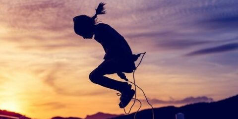 Little girl jumping rope in a violet orange sunset