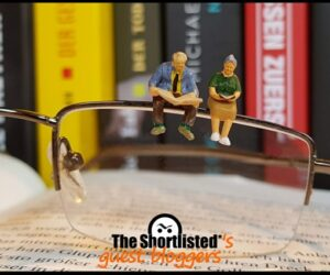 Little toy people on a pair of glass in a library